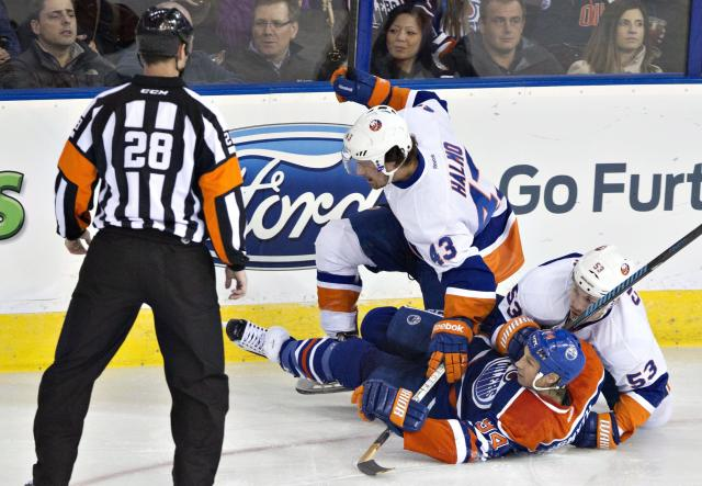 New York Islanders' Mike Halmo and Casey Cizikas (53) pile up on Edmonton Oilers' Ryan Smyth (94) during the first period of an NHL hockey game in Edmonton, Alberta, on Thursday, March 6, 2014. (AP Photo/The Canadian Press, Jason Franson)