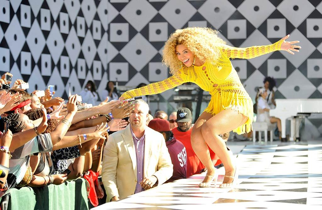 "The ""Single Ladies"" songstress was all smiles while greeting the crowd in a sexy yellow crocheted mini and crazy curly 'do. Kevin Mazur/<a href=""http://www.wireimage.com"" target=""new"">WireImage.com</a> - July 1, 2011"