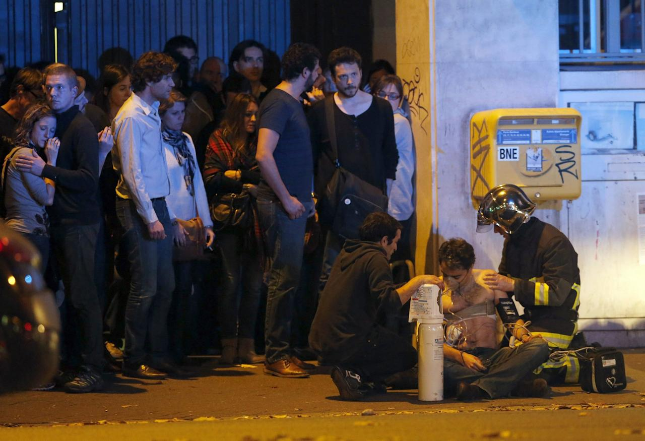 A member of the French fire brigade aids an injured individual near the Bataclan concert hall following fatal shootings in Paris on Nov. 13, 2015.