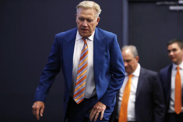 Denver Broncos general manager John Elway, front, leads head coach Vic Fangio into a news conference to talk about the team's first-round selection of Iowa tight end Noah Fant in the NFL Draft Thursday, April 25, 2019, in the team's headquarters in Englewood, Colo. (AP Photo/David Zalubowski)