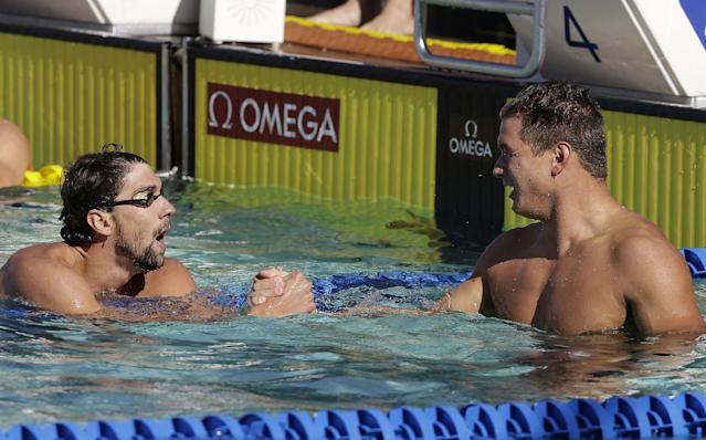 Nathan Adrian, right, is congratulated by Michael Phelps after winning the 100-meter freestyle final during the Santa Clara International Grand Prix swim meet in Santa Clara, Calif., Friday, June 20, 2014. (AP Photo/Jeff Chiu)