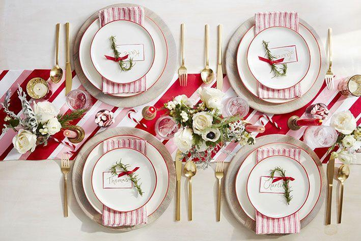 <p>Your guests will feel like they're dining on candy cane lane. Pair a white table cloth with a striped table runner to nail this sweet setting. For an extra touch, bend a twig of rosemary at the top to resemble a candy cane.</p>