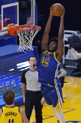 Golden State Warriors center James Wiseman (33) dunks in front of Indiana Pacers forward Domantas Sabonis during the first half of an NBA basketball game in San Francisco, Tuesday, Jan. 12, 2021. (AP Photo/Jeff Chiu)