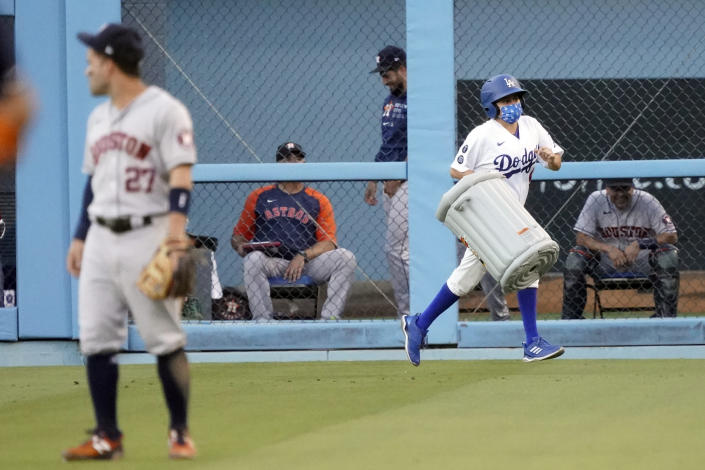 A ball girl removes an inflatable item in the shape of a trash can behind Houston Astros second baseman Jose Altuve (27) during the first inning of the Astros' baseball game against the Los Angeles Dodgers on Tuesday, Aug. 3, 2021, in Los Angeles. (AP Photo/Marcio Jose Sanchez)