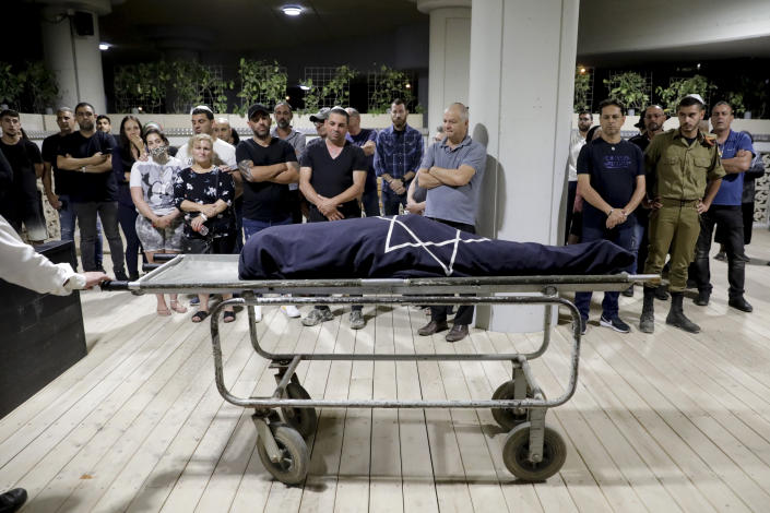 Mourners attend the funeral of Leah Yom Tov, 63, at a cemetery in Rishon Lezion, Israel, Wednesday, May 12, 2021. Yom Tov was killed from a rocket that was fired from Gaza Strip and hit her house in Rishon Lezion on May 11. (AP Photo/Sebastian Scheiner)