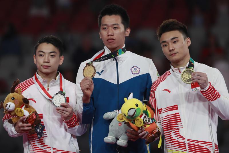 Gold medalist Lee Chih Kai of Taiwan, center, silver medalist Zou Jingyuan, and bronze medalist Sun Wei, both of China, celebrate on the podium during the victory ceremony for men's pommel apparatus final at the 18th Asian Games in Jakarta, Indonesia, Thursday, Aug. 23, 2018. (AP Photo/Dita Alangkara)