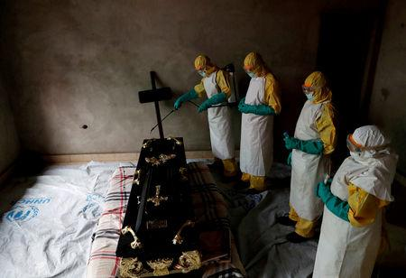 FILE PHOTO: A healthcare worker sprays a room during a funeral of Kavugho Cindi Dorcas who is suspected of dying of Ebola in Beni, North Kivu Province of Democratic Republic of Congo, December 9, 2018. REUTERS/Goran Tomasevic/File Photo