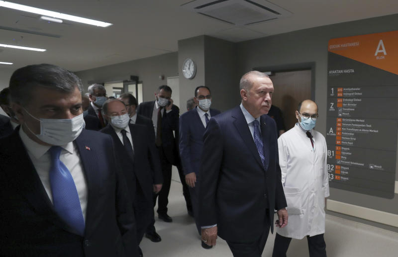 """In this photo provided by the Turkish Presidency, Turkey's President Recep Tayyip Erdogan, front center, arrives to attend the inauguration ceremony for Basaksehir Pine and Sakura City Hospital, in Istanbul, Thursday, May 21, 2020. Japanese Prime Minister Shinzo Abe who participated by videoconference the ceremony has called for international cooperation against the new coronavirus, saying any drug or vaccine developed against the virus must be made """"fairly"""" accessible. (Turkish Presidency via AP)"""