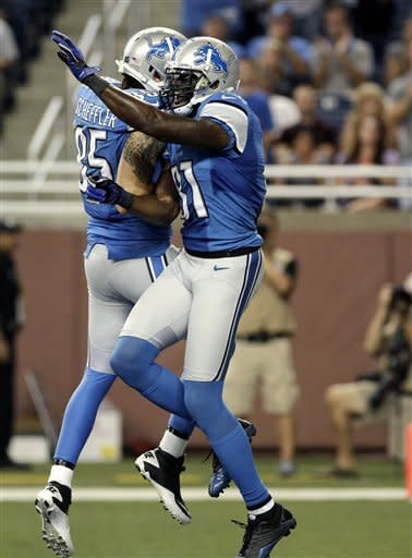 Detroit Lions wide receiver Calvin Johnson celebrates his 24-yard touchdown reception with tight end Tony Scheffler (85) against the Buffalo Bills in the first quarter of their NFL preseason football game in Detroit, Thursday, Aug. 30, 2012. (AP Photo/Duane Burleson)