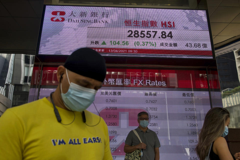 People wearing face masks walk past a bank's electronic board showing the Hong Kong share index at Hong Kong Stock Exchange in Hong Kong Tuesday, April 13, 2021. Asian shares were mostly higher on Tuesday with hopes growing for a global economic rebound despite worries over renewed surges in coronavirus cases. (AP Photo/Vincent Yu)