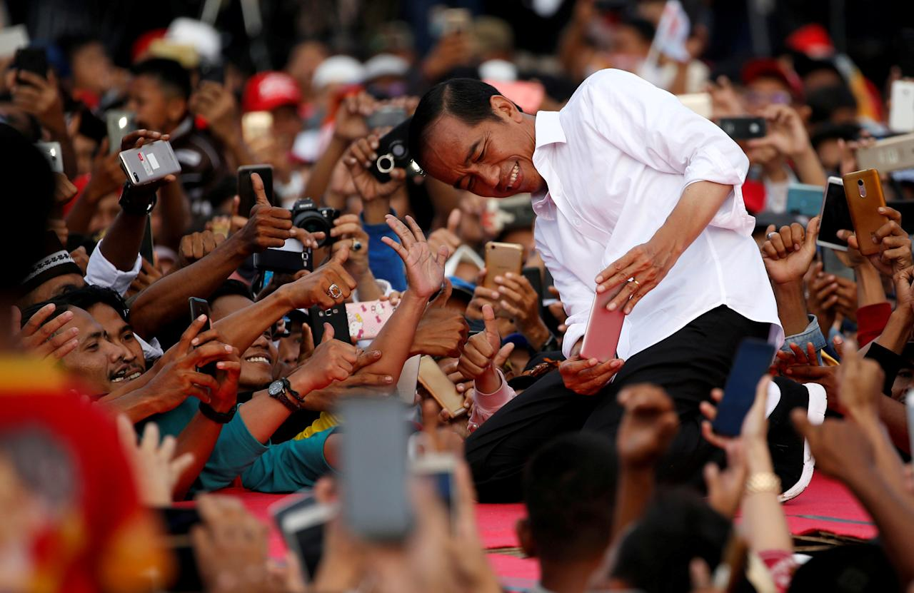Indonesia's presidential candidate for the upcoming general election Joko Widodo takes pictures with his supporters during his first campaign rally at a stadium in Serang, Banten province, Indonesia, March 24, 2019. REUTERS/Willy Kurniawan TPX IMAGES OF THE DAY