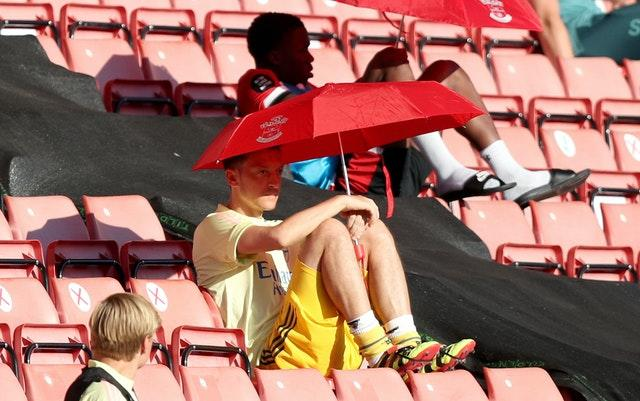 Arsenal's forgotten man Mesut Ozil shelters from the sun under a Southampton umbrella at St Mary's in June. Coronavirus restrictions resulted in substitutes being moved from dugouts and into the stands in order to comply with social distancing rules. Germany midfielder Ozil has not played a single minute of post-lockdown action going into the final day