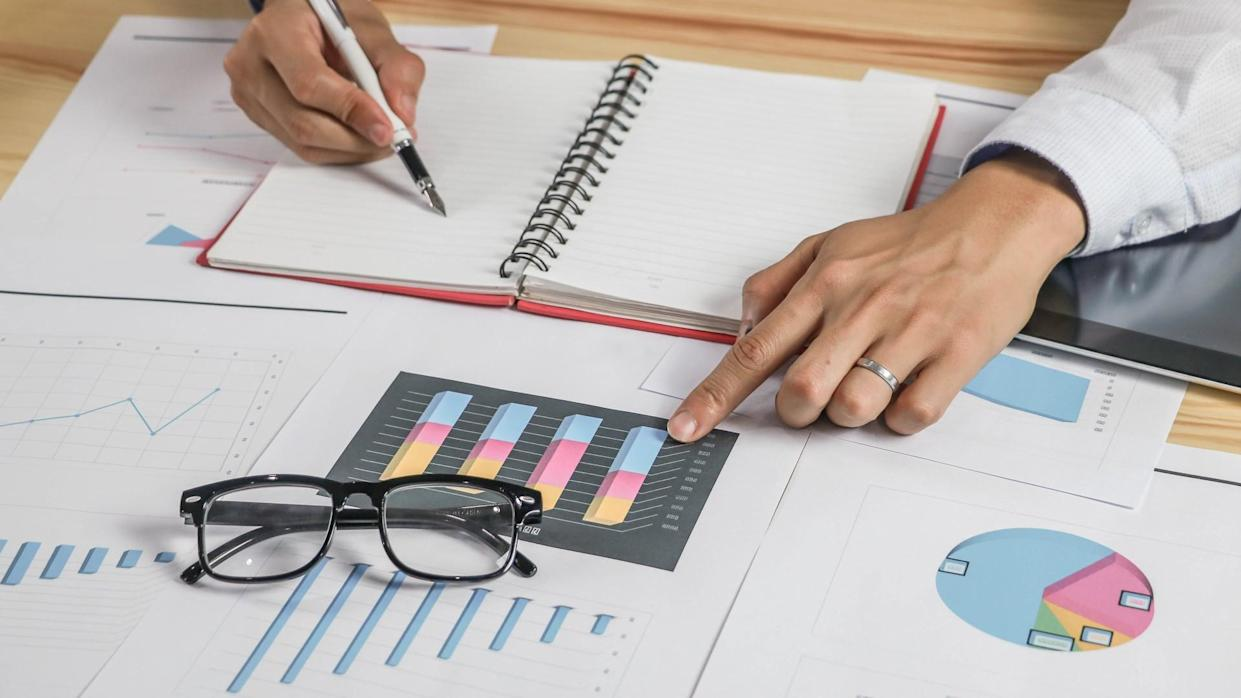 woman writing in noteapd pointing at charts graphs