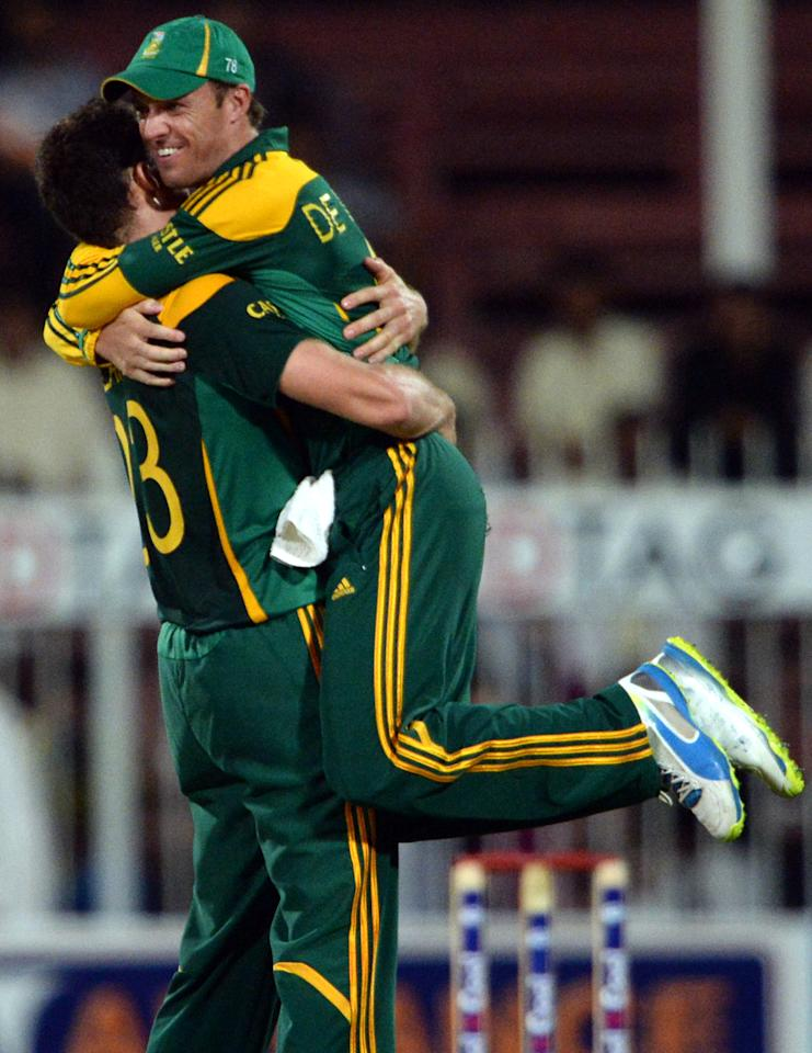 South African captain AB de Villiers (R) celebrates with Ryan McLaren (L) after taking wicket of Pakistan's captain Misbah-ul Haq (unseen) during the fifth and final day international at Sharjah Cricket Stadium in Sharjah on November 11, 2013. Pakistan were chasing a challenging 268-run target after South African skipper AB de Villiers samshed a 102-ball 115 not out in his team's 268-7 run total. South Africa lead the five-match series 3-1.AFP PHOTO/ASIF HASSAN        (Photo credit should read ASIF HASSAN/AFP/Getty Images)