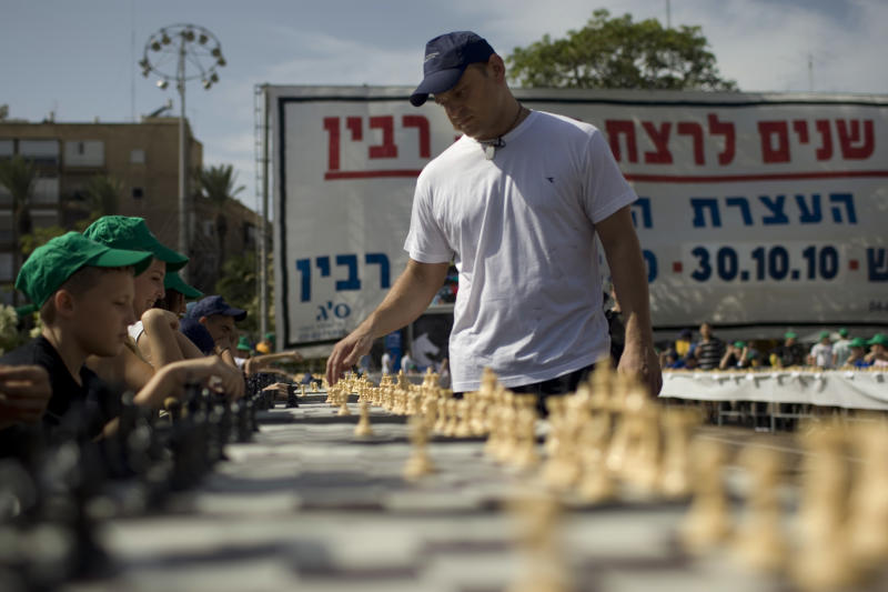 Israeli chess Grandmaster Alik Gershon, right, makes a move during an attempt to break the Guinness world record of simultaneous chess play in Rabin square in Tel Aviv, Israel, Thursday, Oct. 21, 2010. The Jewish Agency and the Israel Chess Federation invited hundreds of chess players, many of them new immigrants from the former Soviet Union to break the Guinness world record for simultaneous chess play against Israeli Grandmaster Alik Gershon. The world record of 500 games played simultaneously is now held by Iran.  (AP Photo/Ariel Schalit)