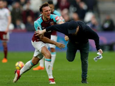 West Ham United's Mark Noble clashes with a fan who invaded the pitch in a match against Burnley. Reuters
