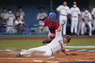 Japan's Tetsuto Yamada, bottom, is tagged out by Dominican Republic catcher Charlie Valerio while trying to score on a double hit by Masataka Yoshida in the eighth inning of a baseball game at the 2020 Summer Olympics, Wednesday, July 28, 2021, in Fukushima, Japan. (AP Photo/Jae C. Hong)
