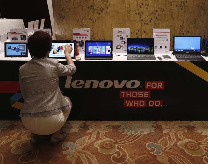 A woman tries a Lenovo tablet on display during a news conference announcing the company's annual results in Hong Kong