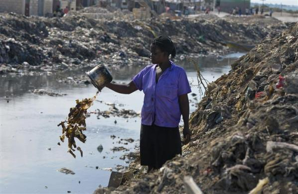 A woman discards waste into a canal in the slum area of Cite de Dieu, just outside Port-au-Prince March 13, 2012.