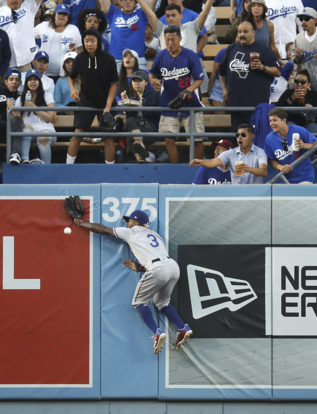 Fans watch as Texas Rangers' Delino DeShields misses an RBI double hit by Los Angeles Dodgers' Yasiel Puig during the second inning of a baseball game, Tuesday, June 12, 2018, in Los Angeles. (AP Photo/Jae C. Hong)