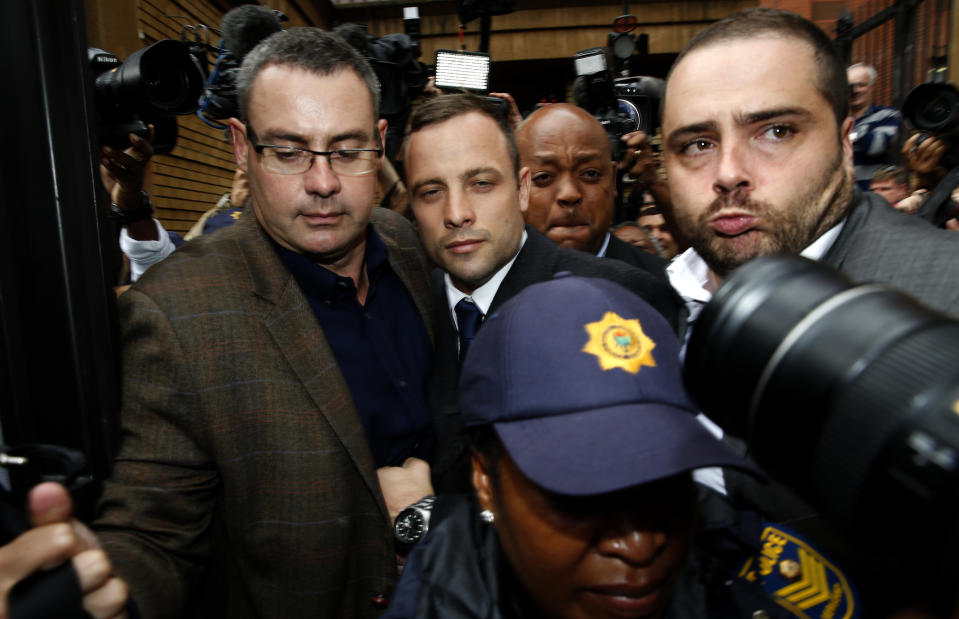 Olympic and Paralympic track star Oscar Pistorius (C) leaves after his trial at the North Gauteng High Court in Pretoria March 4, 2014. Pistorius is on trial for murdering his girlfriend Reeva Steenkamp at his suburban Pretoria home on Valentine's Day last year. He says he mistook her for an intruder. REUTERS/Siphiwe Sibeko (SOUTH AFRICA - Tags: SPORT ATHLETICS CRIME LAW)