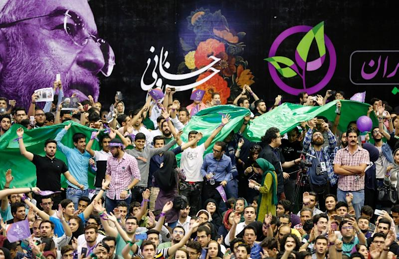 Thousands at an election rally for President Hassan Rouhani on May 13, 2017 chant the names of reformist leaders still locked away by the regime (AFP Photo/ATTA KENARE)
