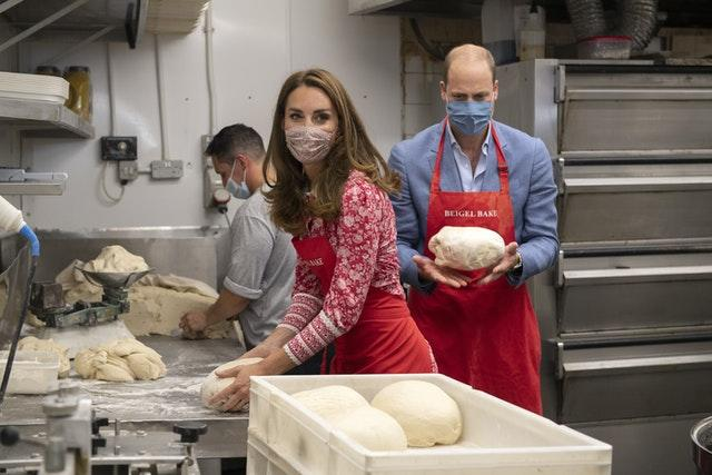 The Duke and Duchess of Cambridge knead dough during a visit to the Beigel Bake Brick Lane Bakery in London