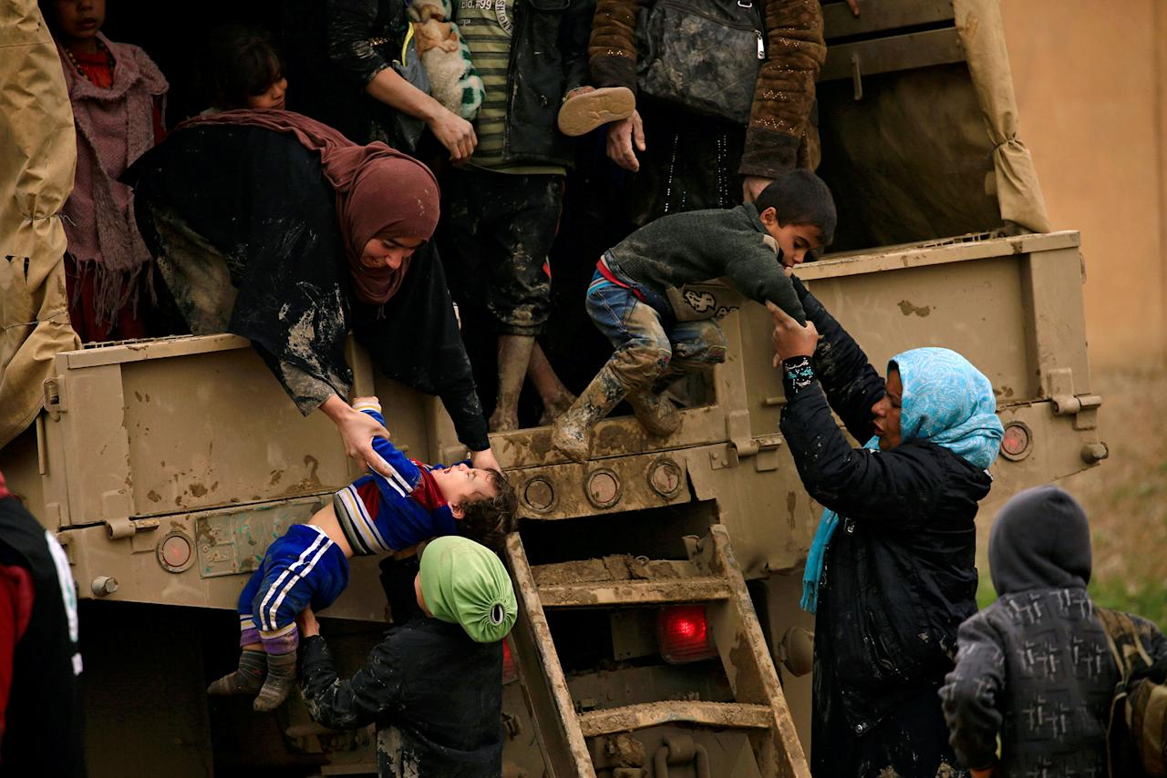 <p>Displaced Iraqi women who fled their homes during a battle between Iraqi forces and Islamic State militants, try to get out of a vehicle with their children at a checkpoint, to be transfer to Hammam al-Alil camp, in Mosul, Iraq, March 20, 2017. (Thaier Al-Sudani/Reuters) </p>