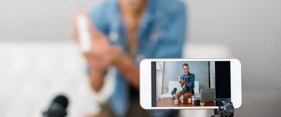 close up of smartphone on tripod, filming woman displaying product while sitting on a couch