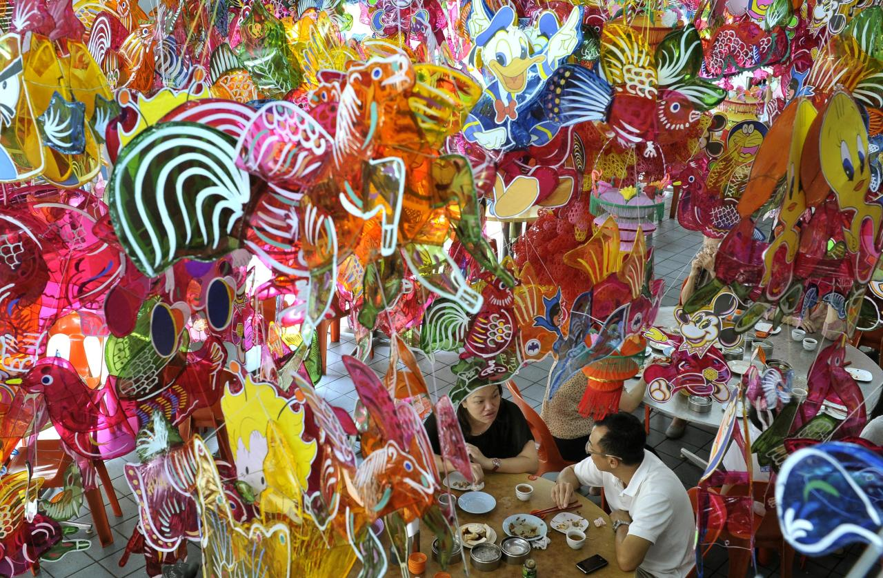 People eat under Chinese lanterns displayed at a restaurant as part of celebrations for the upcoming Mid-Autumn Festival on Penang Island, Malaysia, Tuesday, Sept. 25, 2012.  (AP Photo/ Gary Chuan)