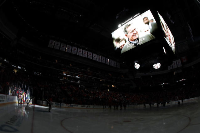 A moment of silence is held for former United States President George H.W. Bush prior to an NHL hockey game between the New Jersey Devils and the Winnipeg Jets, Saturday, Dec. 1, 2018, in Newark, N.J. Bush died Friday, Nov. 30, 2018. (AP Photo/Julio Cortez)
