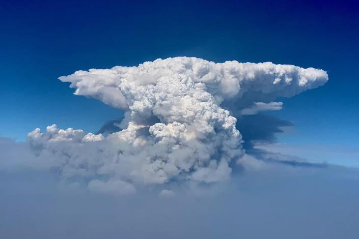"""In this photo taken with a drone provided by the Bootleg Fire Incident Command, a pyrocumulus cloud, also known as a fire cloud, is seen over the Bootleg Fire in southern Oregon on Wednesday, July 14, 2021. Smoke and heat from a massive wildfire in southeastern Oregon are creating """"fire clouds"""" over the blaze — dangerous columns of smoke and ash that can reach up to 30,000 feet (9,144 meters) and are visible for more than 100 miles (160 kilometers) away. Authorities have put these clouds at the top of the list of the extreme fire behavior they are seeing on the Bootleg Fire, the largest wildfire burning in the U.S. (Bootleg Fire Incident Command via AP)"""