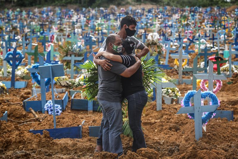 People mourn during a mass burial of coronavirus pandemic victims on May 19, 2020, in Manaus, Brazil. Brazil has over 270,000 confirmed COVID-19 cases and more than 17,000 deaths caused by the virus. (Andre Coelho via Getty Images)