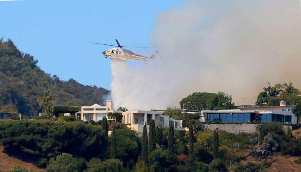 PHOTO: A helicopter makes a water drop as flames threaten homes on a ridgeline as a wildfire threatens homes in the Pacific Palisades area of Los Angeles, Oct. 21, 2019. (Reed Saxon/AP)