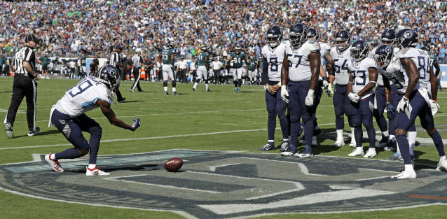<p>Tennessee Titans wide receiver Tajae Sharpe (19) rolls the football toward his teammates to knock them over like bowling pins as they celebrate a touchdown catch by Sharpe against the Philadelphia Eagles in the second half of an NFL football game Sunday, Sept. 30, 2018, in Nashville, Tenn. (AP Photo/James Kenney) </p>
