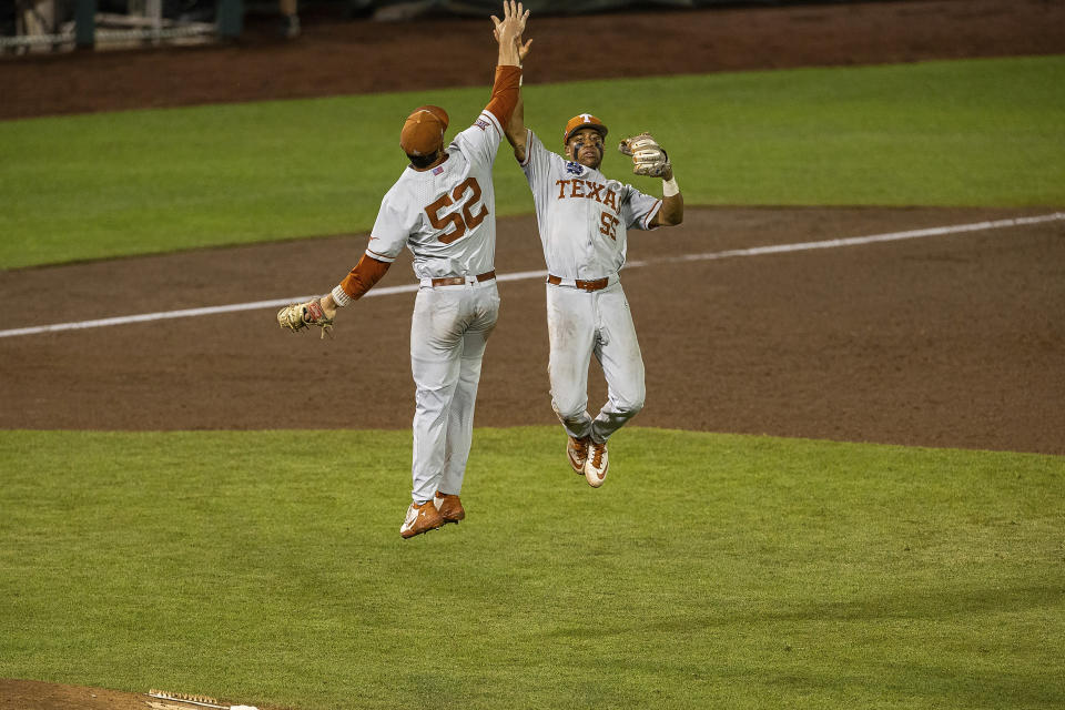 Texas' Camryn Williams (55) and Zach Zubia (52) give each other a high five celebrating their win over Virginia during a baseball game in the College World Series Thursday, June 24, 2021, at TD Ameritrade Park in Omaha, Neb. (AP Photo/John Peterson)