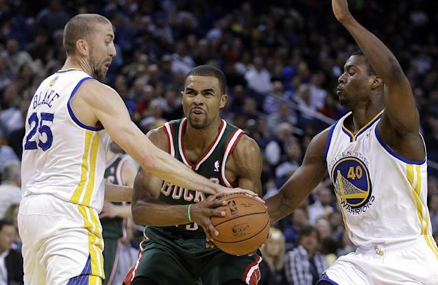 Milwaukee Bucks' Ramon Sessions, center, looks to pass between Golden State Warriors' Steve Blake, left, and Harrison Barnes (40) during the first half of an NBA basketball game Thursday, March 20, 2014, in Oakland, Calif. (AP Photo/Ben Margot)