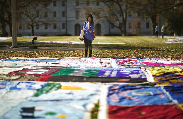 <p>Student Christina Batipps browses over a display of AIDS memorial quilt panels on display as part of World AIDS Day at Emory University, Dec. 1, 2014, in Atlanta. (AP Photo/David Goldman) </p>