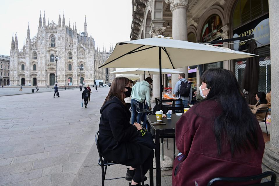 People sit at a cafe's terrace close to Duomo square on April 26, 2021 in central Milan. - Bars, restaurants, cinemas and concert halls will partially reopen across Italy Monday in a boost for coronavirus-hit businesses, as parliament debates the government's 220-billion-euro ($266-billion) EU-funded recovery plan. After months of stop-start restrictions imposed to manage its second and third waves of Covid-19, Italy hopes this latest easing will mark the start of something like a normal summer. (Photo by Miguel MEDINA / AFP) (Photo by MIGUEL MEDINA/AFP via Getty Images)