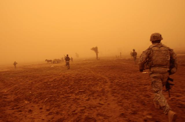<p>In the orange fog of an Iraqi sandstorm, US troops run up and fire warning shots at three Iraqi men in a field who started running from their patrol May 16, 2008 in Baghdad, Iraq. One of the three men was shot in the leg by the advancing US troops, and started bleeding heavily. He was immediately treated by the US medic traveling with the platoon and transported to the nearest US base for medical care, and is expected to recover. The other two men were arrested by the troops and brought in for investigation. (Photo by Chris Hondros/Getty Images) </p>