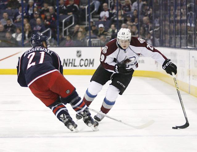 Columbus Blue Jackets' David Wisniewski (21) tries to slow down Colorado Avalanche's Nathan MacKinnon (29) during the first period of an NHL hockey game, Tuesday, April 1, 2014, in Columbus, Ohio. (AP Photo/Mike Munden)