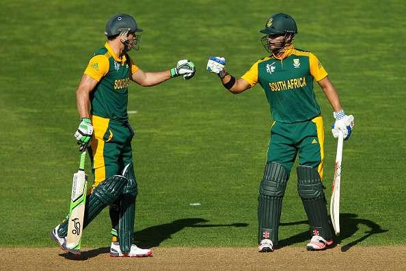 WELLINGTON, NEW ZEALAND - MARCH 12: AB de Villiers (L) and JP Duminy of South Africa bump fists while batting during the 2015 ICC Cricket World Cup match between South Africa and the United Arab Emirates at Wellington Regional Stadium on March 12, 2015 in Wellington, New Zealand. (Photo by Hagen Hopkins/Getty Images)