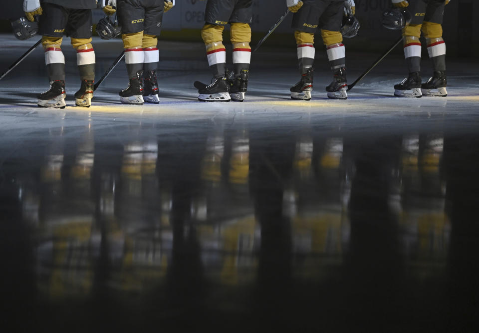 The Vegas Golden Knights stand for the national anthem before an NHL hockey game against the St. Louis Blues on Saturday, May 8, 2021, in Las Vegas. (AP Photo/David Becker)