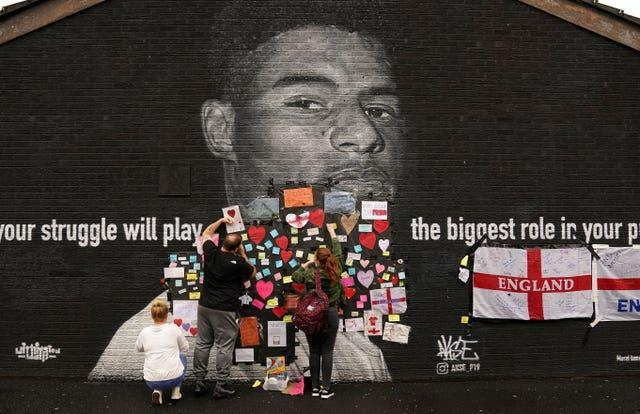 People place messages of support on top of bin liners that were taped over offensive wording on the mural of England forward Marcus Rashford