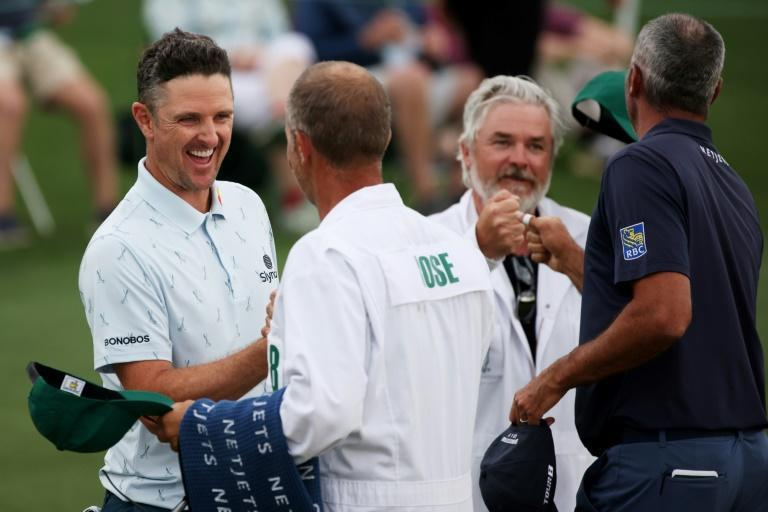 England's Justin Rose, left, bumps fists with caddie David Clark after firing a seven-under par 65 in Thursday's opening round of the Masters