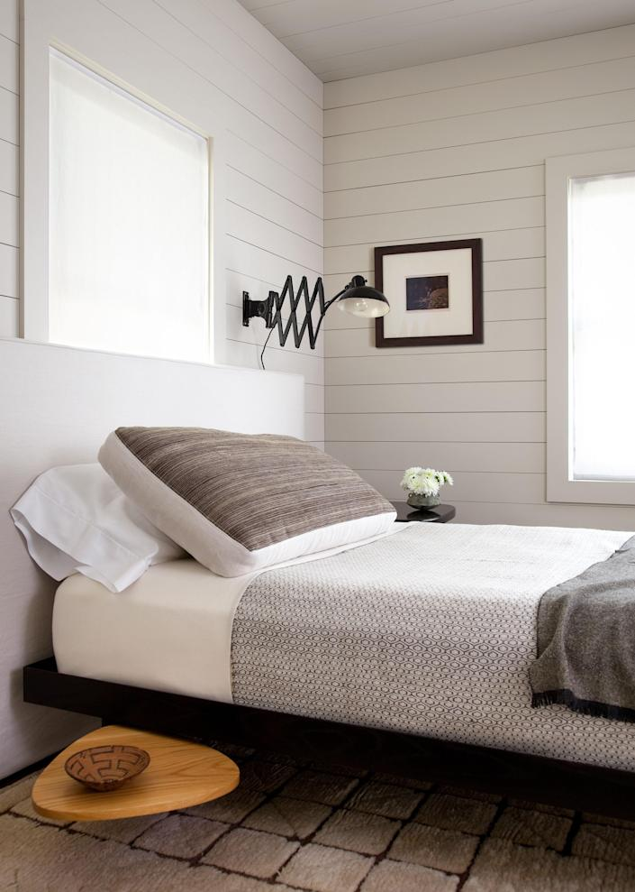 A Jean Prouve daybed and Christian Dell scissor lamp are installed in a guest bedroom.