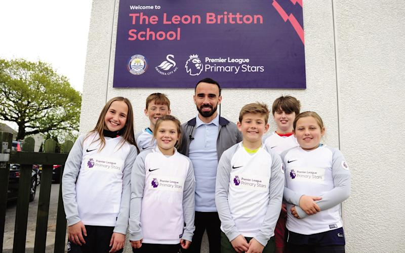 Britton with children at the Leon Britton School - Credit: Getty Images