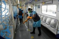 Workers clean a carriage of a commuter train after passengers got out following the resumption of metro services after more than five months of shutdown at a station in Hyderabad on September 7, 2020. (Photo by NOAH SEELAM/AFP via Getty Images)