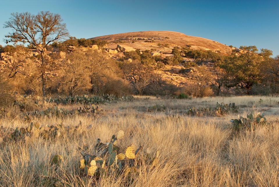 """<p><strong>Let's start big picture.</strong><br> This mystical pink granite dome called Enchanted Rock, is ideal for camping and stargazing, but most people come to spend half a day hiking and exploring. It's a steep walk to the summit, but even a novice can make it up, with a few breaks to sit and enjoy the views. Once at the top, there are natural rock formations and trails lined with Texas wildflowers to explore.</p> <p><strong>Any standout features or must-sees?</strong><br> Once you've reached the top, find your way to the dome's cave. It doesn't look like much, so keep your eyes peeled for the line of people that typically forms at the cave's entrance. Not meant for the claustrophobic, the cave is very dark, so be sure to bring a flashlight if you plan on exploring.</p> <p><strong>Was it easy to get around?</strong><br> A trail map is available for purchase at the base (as are walking sticks) but neither is totally necessary as it's straightforward to get to the top—simply follow the crowds. Note that it's best to arrive early: Parking is limited and the gates close when the lot is full, then reopen as spots become available. Likewise, take caution during inclement weather, as paths close during or after heavy rains. Also note, booking your day and camping passes in advance on the <a href=""""https://tpwd.texas.gov/state-parks/park-reservation-information/reservations"""" rel=""""nofollow noopener"""" target=""""_blank"""" data-ylk=""""slk:parks website"""" class=""""link rapid-noclick-resp"""">parks website</a> is encouraged.</p> <p><strong>All said and done, what—and who—is this best for?</strong><br> Enchanted Rock is extremely popular with families. This is an activity outdoor enthusiasts can't miss, but the rock formations and views are mesmerizing for anyone who is able to carve out the time for 360-degree views of the Texas Hill Country.</p>"""