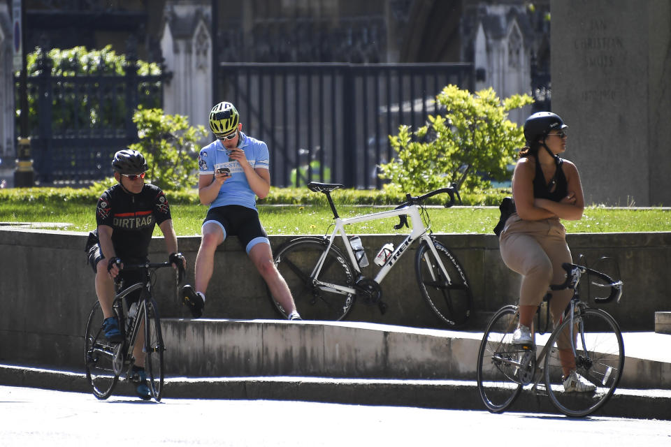 Cyclists wait at Parliament Square, in London, Monday, May 18, 2020. Large areas of London are to be closed to cars and vans to allow people to walk and cycle safely as the coronavirus lockdown is eased. (AP Photo/Alberto Pezzali)